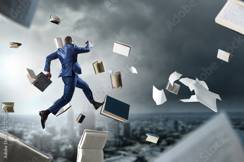 Fotografie, Obraz  Back view of black businessman with briefcase running among flying books and pap
