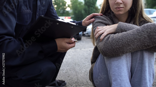 Officer trying to calm down female victim of car accident, shocked girl crying Fototapeta