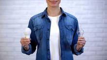 Woman Choosing Between Energy Saving Led Bulb And Incandescent Lamp, Efficiency