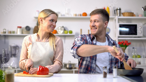 Fényképezés  Young vegan couple cooking vegetables, healthy nutrition, happy time together