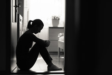 Sad Woman Sitting At Home In A Dark Room.