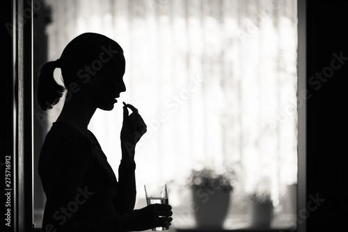 Fototapeta Female taking pill medication in a home setting.  obraz