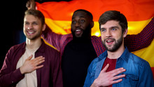 Spanish Multiethnic Male Football Fans Singing National Anthem And Waving Flag