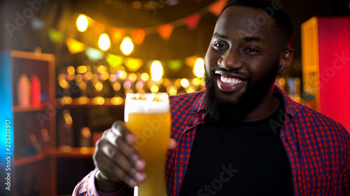 Fotografía  Happy african american man holding glass with fresh and cold light beer, pastime