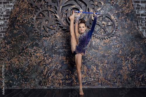 Girl gymnast in a blue suit with sparkles makes exercise with maces gym on the background of the brown wall with gears and smiling Tablou Canvas
