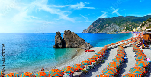 Panoramic view over colorful umbrellas at a beach in the Cinque Terre village of Monterosso
