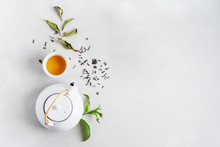 Tea Concept With White Tea Set Of Cups And Teapot Surrounded With Fresh Tea Leaves On Concrete Background With Copy Space.