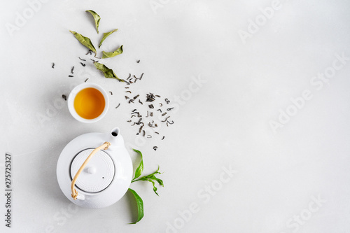 Obraz na płótnie Tea concept with white tea set of cups and teapot surrounded with fresh tea leaves on concrete background with copy space