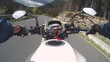 Motorcyclist Rides on a Beautiful Landscape Mountain Road in Romania. First-person view. POV. Biker riding down a scenic and empty road toward the mountains