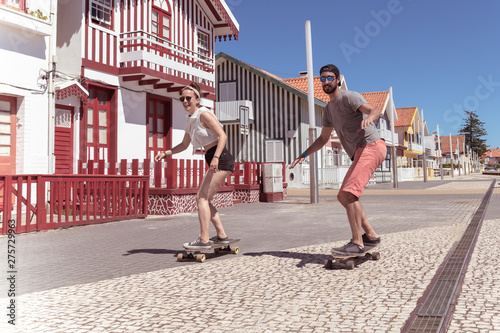plakat Young active couple enjoying a summer sunny day skateboarding