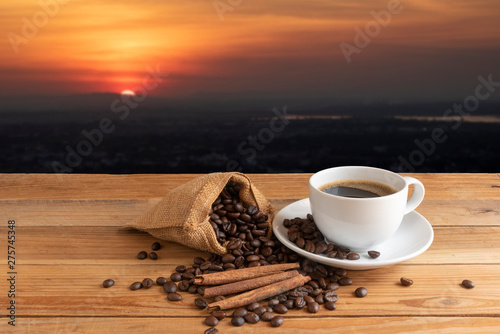 Fototapeta cennamon and roasted coffee with white coffe cup on wooden desk on landscape view obraz