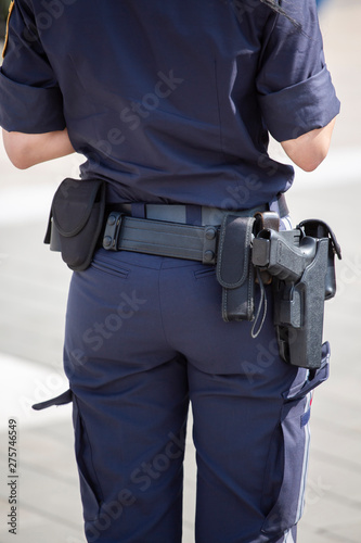 Fototapeta Armed Austrian Poliewoman from behind showing her navy blue uniform and pistol