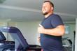 chubby man walking on running track, warming up on gym treadmill.