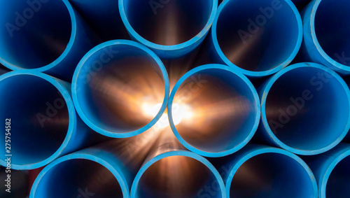 Valokuvatapetti Group of blue water pipes That is stacked into a graphic format With light comin
