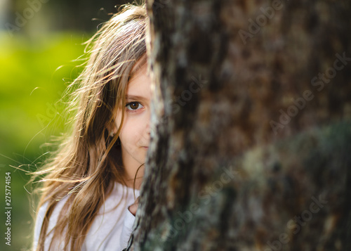 portrait of young girl hiding behind the tree Wallpaper Mural