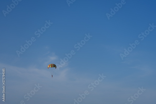 Foto op Canvas Luchtsport A multi-colored parachute over the sea against a clear blue sky.