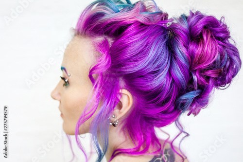 Portrait of a young beautiful woman with colored hair. Bright shades of blue and purple, gradient hair.