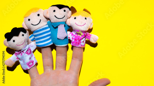 Foto auf Leinwand Gelb Puppet theater. Hand wearing finger family members puppets: mum, dad, father, mom, daughter, son. happy family concept.