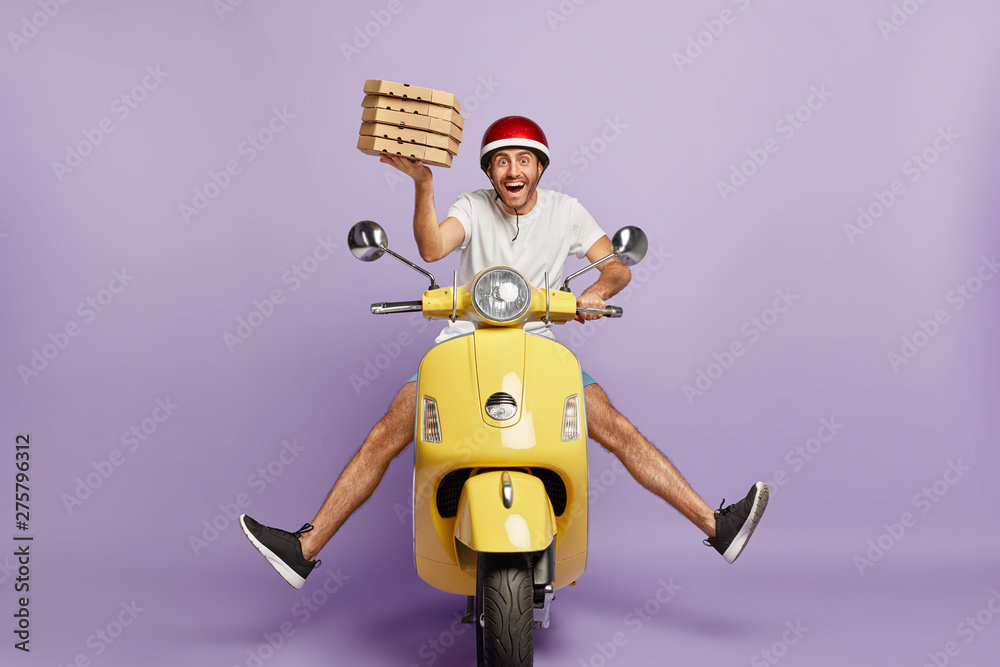 Fototapety, obrazy: Busy deliveryman being in hurry, carries cardboard boxes with pizza, delivers to customers, poses on yellow scooter, wears helmet, white t shirt and sportshoes, spreads legs, has happy expression