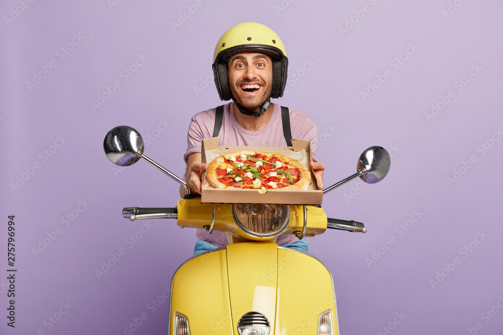 Fototapety, obrazy: Friendly looking punctual pizzaman has good time management skills, arrives always in time, shows delicious pizza for customer, hopes for getting tip, wears yellow helmet, rides on fast motorcycle