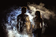 The couple standing near the smoke in the dark