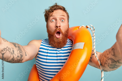 Recess Fitting Relaxation Horizontal shot of young shocked lifeguard makes selfie portrait, has astonished expression, poses with inflated lifering, cannot believe in unexpected rumors. People, summer rest and safety concept