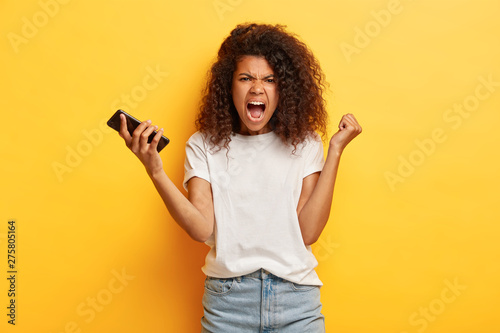 Outraged dark skinned woman raises clenched fist, holds modern cell phone, screa Canvas Print