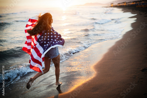 Photo Stands Height scale Happy woman running on beach while celebrateing independence day and enjoying freedom in USA