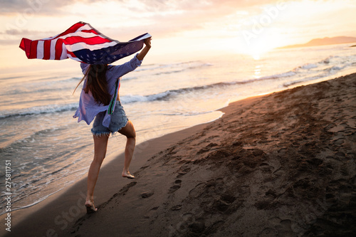 Fotobehang Hoogte schaal Happy woman running on beach while celebrateing independence day and enjoying freedom in USA