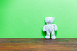 Leinwanddruck Bild - Teddy bear on old wood and green wall background