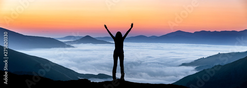 Fotografiet  Glückliche Frau auf einem Gipfel über der Nebeldecke