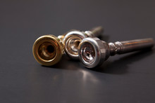Three Trumpet Mouthpieces, Gold And Silver  Against Black Background