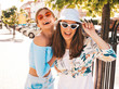 Two young beautiful smiling hipster girls in trendy summer clothes and panama hat. Sexy carefree women posing on street background.Positive models having fun in sunglasses.Hugging