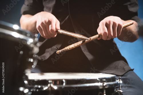 Close-up of a male drummer's hand holding drum sticks while sitting behind a drum set - 275824500
