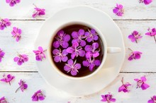 White Cup With A Tea From The Flowers Of Fireweed  On White Wooden Background Top View
