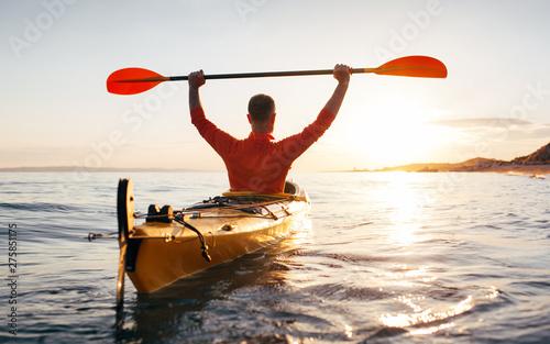 Fotografia  Rear view of active senior man holds kayak paddles high toward sun