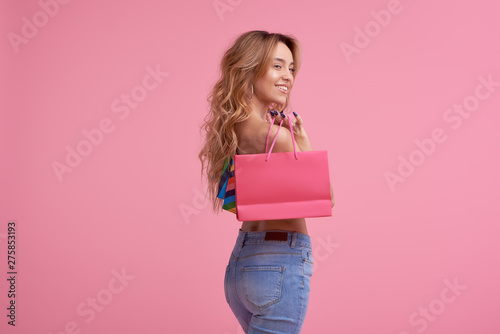 Fotografía  Portrait of an excited beautiful smiling girl wearing colorful clothes holding shopping bag isolated over pink background