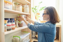 Interior Of Wooden Pantry With Products For Cooking. Adult Woman Taking Kitchenware And Food From The Shelves