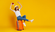 Concept Of Travel. Happy Woman Girl With Suitcase And  Passport On  Yellow Background.