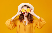 Cheerful Young Curly Woman Girl With   Orange   On  Yellow   Background
