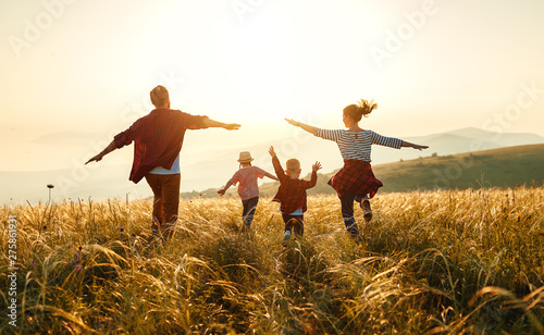 Canvas Prints Height scale Happy family: mother, father, children son and daughter on sunset.