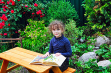 Landscaping Green Garden With Flowers And An Alpine Slide, In The Foreground Girl Sitting At A Wooden Table On A Bench And Reading A Book On Gardening.