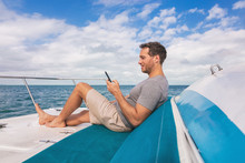 Boat Man Using Mobile Phone Texting On Satellite Internet While Relaxing On Deck Of Yacht Luxury Lifestyle.
