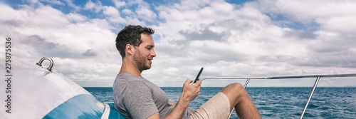 Yacht luxury lifestyle young man using cellphone banner panorama. Person relaxing on deck texting sms message on mobile phone under the sun summer holidays.