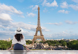 Fototapeta Paryż - Young traveler woman in white hat looking at Eiffel tower, famous landmark and travel destination in Paris