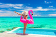 canvas print picture - Vacation Woman in bikini and inflatable pink flamingo toy mattress float by pool