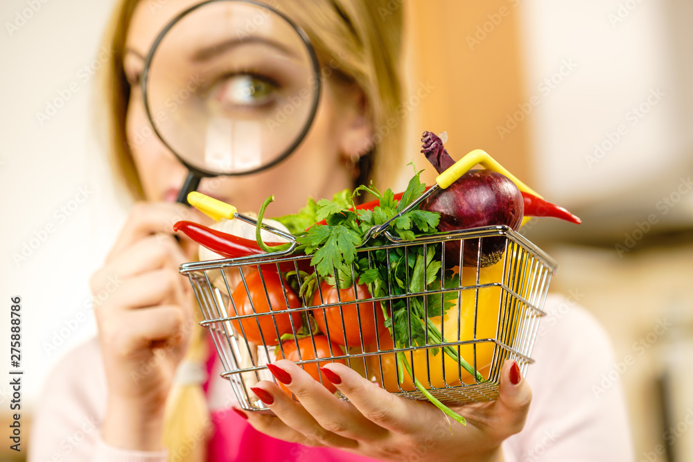 Fototapeta Woman investigating shopping backet with vegetables
