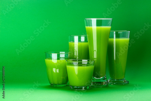 Poster Pays d Europe Green juice on green colored background with copy space for text, fresh apple and celery cocktail