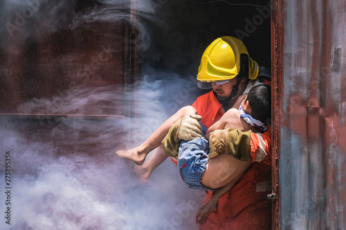 Obraz na plátně Firefighter holding child boy to save him in fire and smoke,Firemen rescue the boys from fire