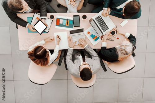 Fotografía  Top view of Caucasian business people in formal wear sitting in boardroom at desk and analyzing data